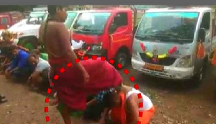 Priest blesses devotees by placing foot on their heads